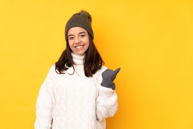 제품을 제시하기 위해 측면을 가리키는 격리 된 노란색에 겨울 모자와 젊은 여자