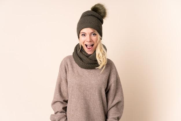 驚きの表情で分離された冬の帽子を持つ若い女性