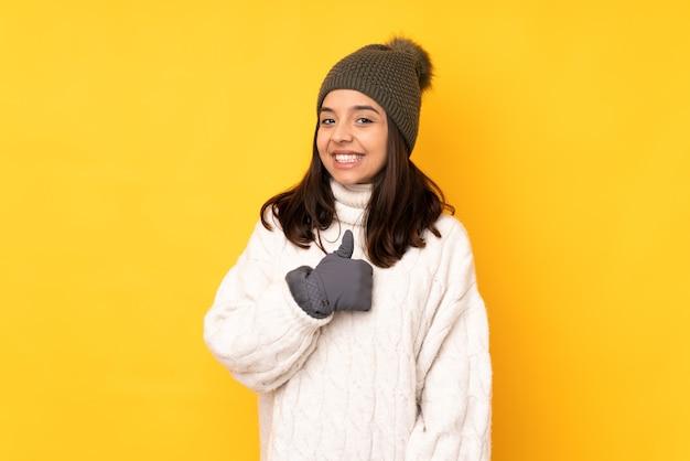 제스처를 엄지 손가락을주는 고립 된 노란색 배경 위에 겨울 모자와 젊은 여자
