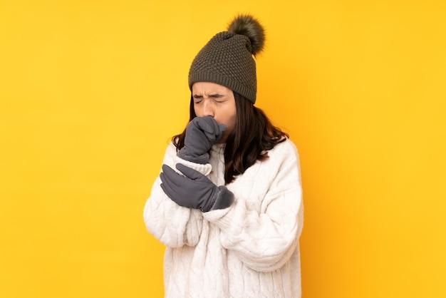 Молодая женщина в зимней шапке на изолированном желтом фоне страдает от кашля и плохо себя чувствует