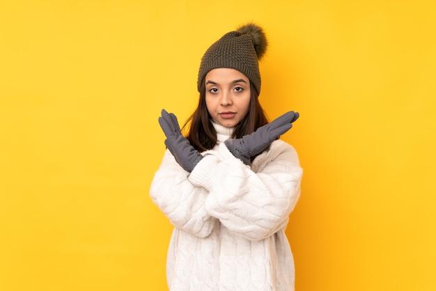 Молодая женщина в зимней шапке на изолированном желтом фоне, не делая жестов