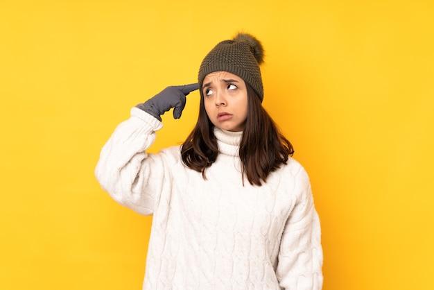머리에 손가락을 넣어 광기의 제스처를 만드는 고립 된 노란색 배경 위에 겨울 모자와 젊은 여자
