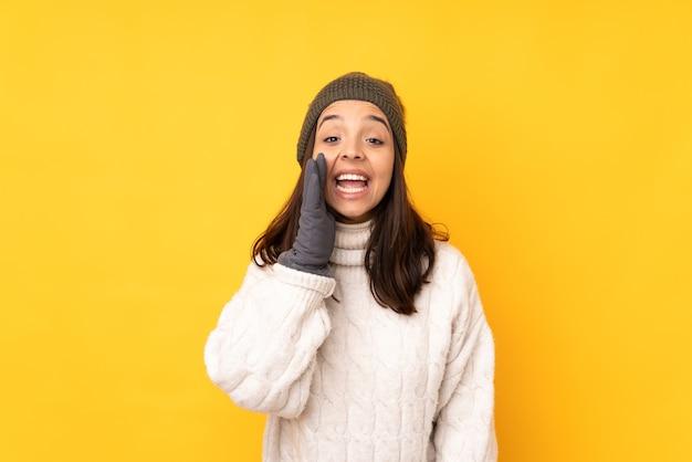 Молодая женщина в зимней шапке на изолированном желтом фоне кричит с широко открытым ртом