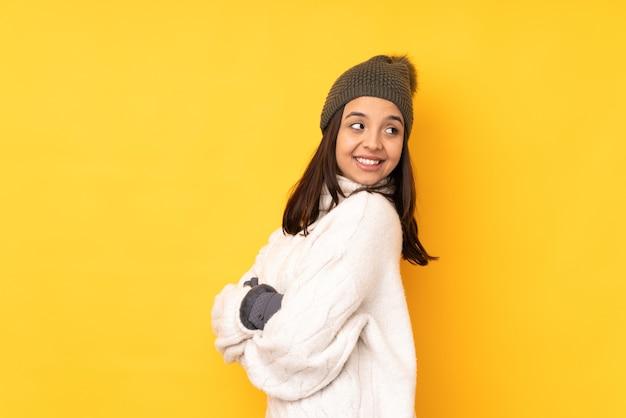 腕を組んで幸せな孤立した黄色の背景の上の冬の帽子を持つ若い女性