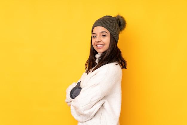 팔을 교차 하 고 기대와 격리 된 노란색 배경 위에 겨울 모자와 젊은 여자