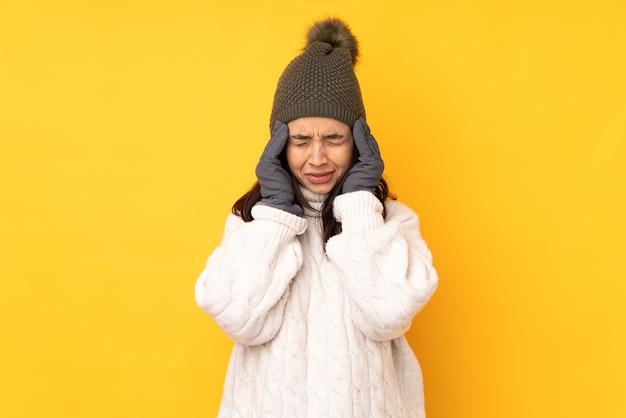 두통으로 고립 된 노란색 배경 위에 겨울 모자와 젊은 여자