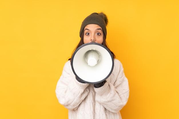 확성기를 통해 외치는 고립 된 노란색에 겨울 모자와 젊은 여자