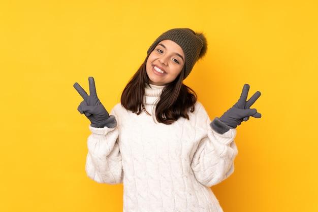 Молодая женщина в зимней шапке над изолированной желтой стеной показывает знак победы обеими руками