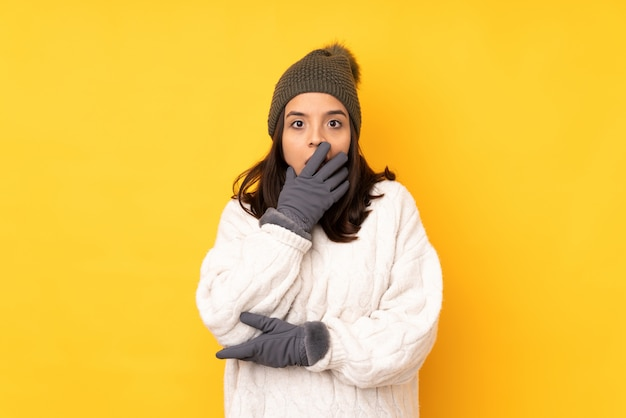 Young woman with winter hat surprised and shocked while looking right