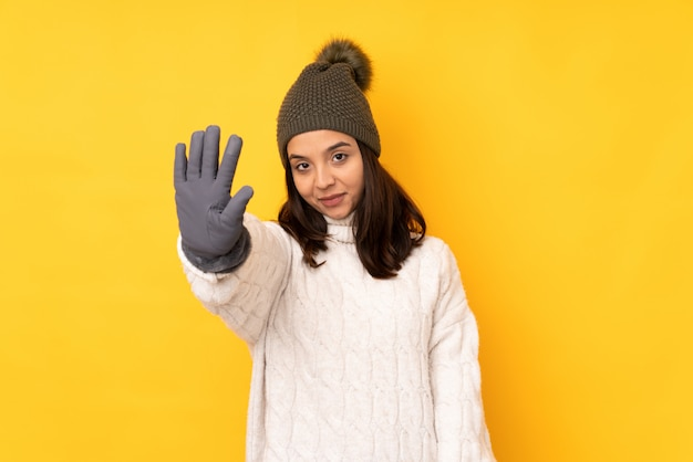 Young woman with winter hat over yellow wall counting five with fingers