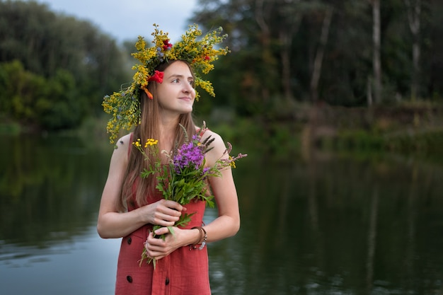 Young woman with wreath on the head of wildflowers on lake background.