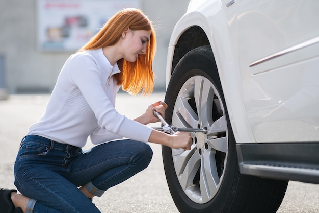 Young woman with wrench changing wheel on a broken car.