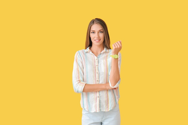 Young woman with wristwatch on color