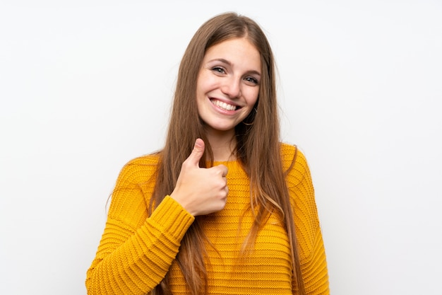 Young woman with yellow over isolated white wall giving a thumbs up gesture