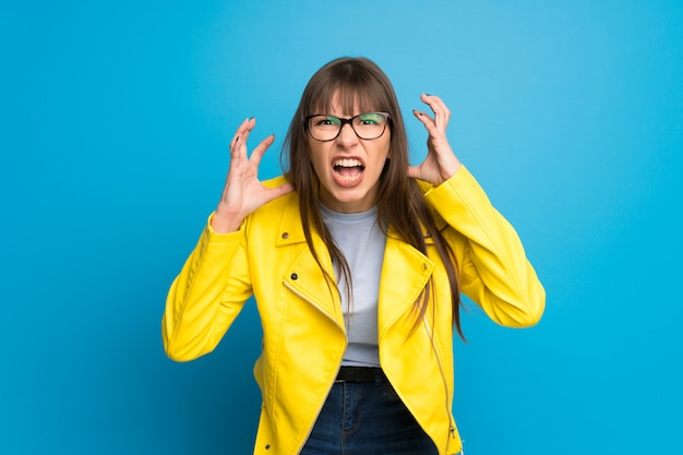 Young woman with yellow jacket on blue background frustrated by a bad situation