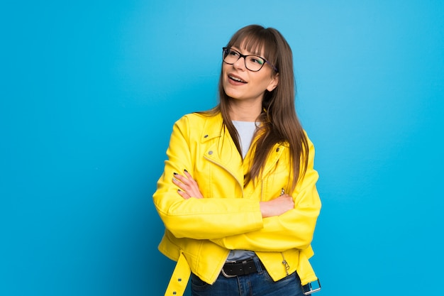 Young woman with yellow jacket on blue background keeping the arms crossed while smiling