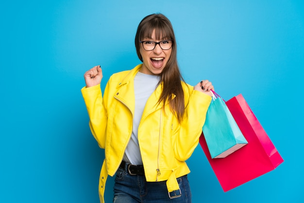 Young woman with yellow jacket on blue  holding a lot of shopping bags in victory position