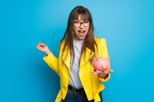 Young woman with yellow jacket on blue  surprised while holding a piggybank