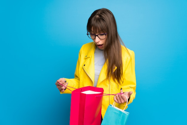 Young woman with yellow jacket on blue wall surprised while holding a lot of shopping bags