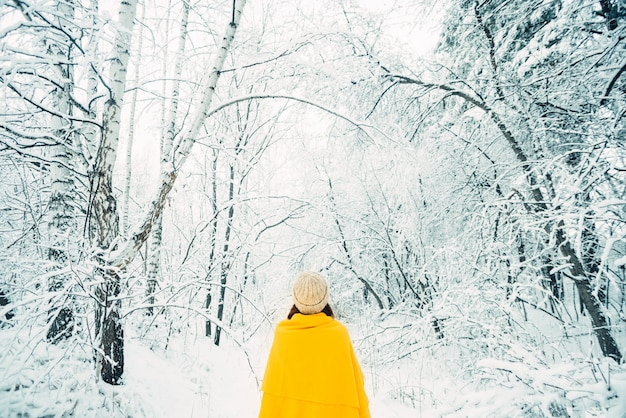 Young woman with a yellow plaid in a snowy forest, rear view. winter mood.