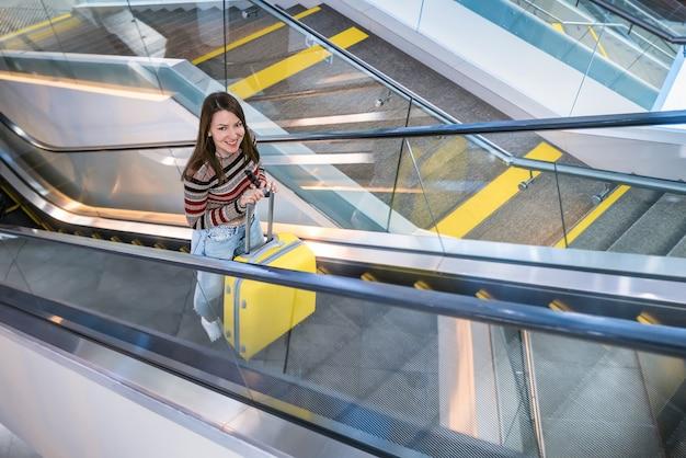 Молодая женщина с желтым чемоданом. путешественник в аэропорту.
