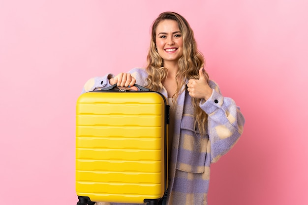 Young woman with yellow travel suitcase