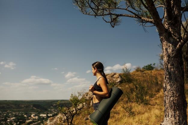 요가 매트와 젊은 여자 야외 요가 연습을 준비합니다.
