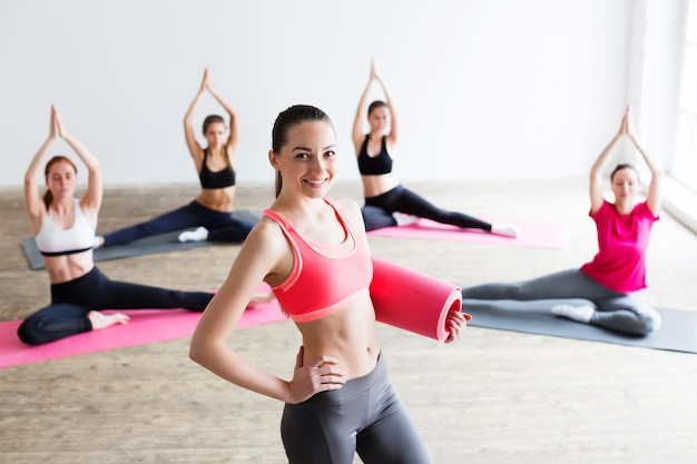 Молодая женщина с ковриком для йоги в тренажерном зале