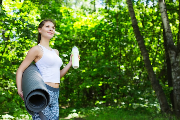 Young woman with a yoga mat outdoors.