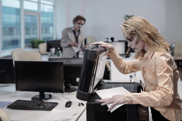 Молодая женщина с зомби-жиром на лице и руках, стоящая у ксерокопии и открывающая крышку перед копированием документов