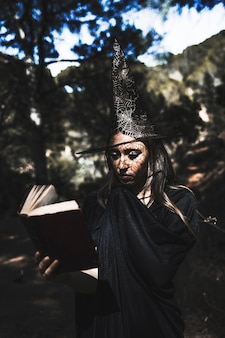 Young woman in wizard costume reading book in forest