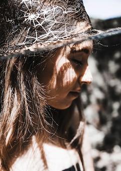 Giovane donna in cappello da mago che chiude gli occhi