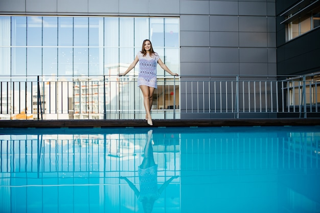 Young woman woman in beautiful lace dress beside rooftop pool