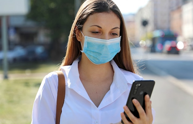Young woman woman wearing a mask using a mobile phone in the street