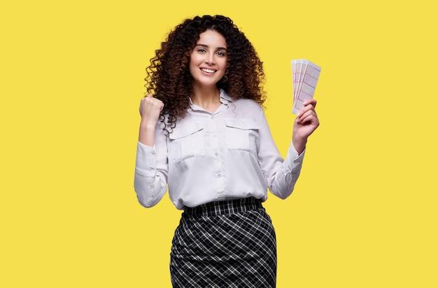 若い女性が宝くじに当選しました。黄色の孤立した背景に宝くじを保持している幸せな女性。