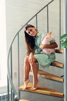 Giovane donna sulle scale di legno in casa moderna.