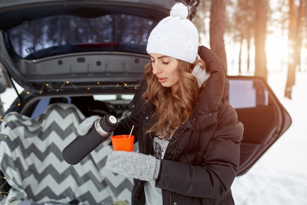 Young woman in woolen hat and black jacket stand near trunk of the car