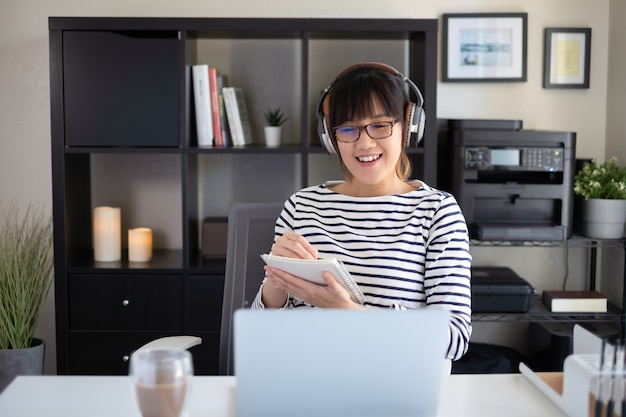 Young woman work at home office . smiling and using head phone.