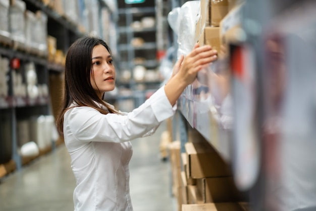 창고 상점에서 재고를 확인하는 젊은 여성 노동자