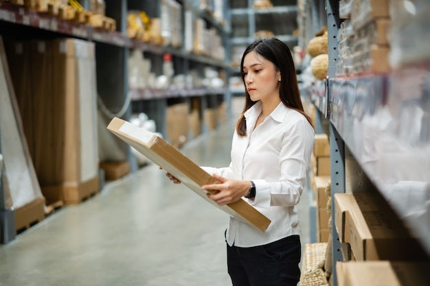 Young woman worker checking inventory in the warehouse store