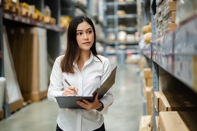 Young woman worker holding clipboard and checking inventory in the warehouse store