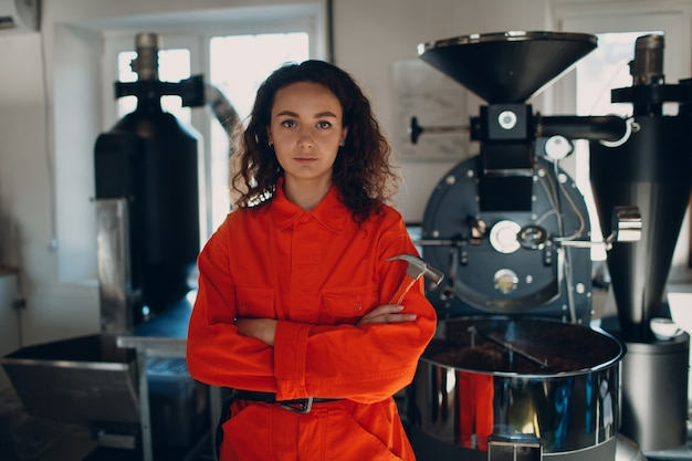 Young woman worker with hammer in orange suit in workshop with coffee roaster machine during coffee roasting process.