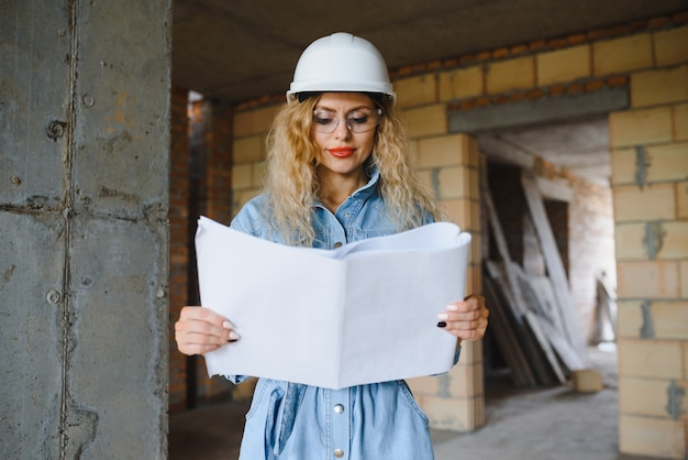 Young woman worker with a white helmet on the construction site.