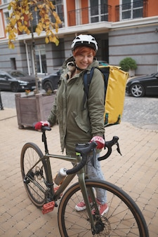 Young woman working as delivery courier in the city using her bicycle