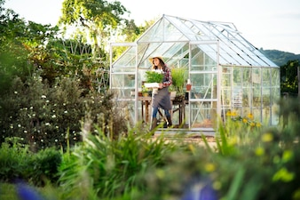 Young woman working at a glass greenhouse