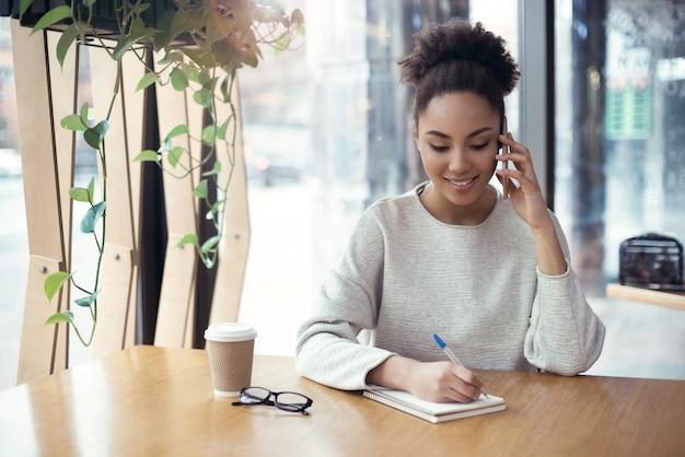 Молодая женщина, работающая в творческом стильном офисе, сидя разговаривает о