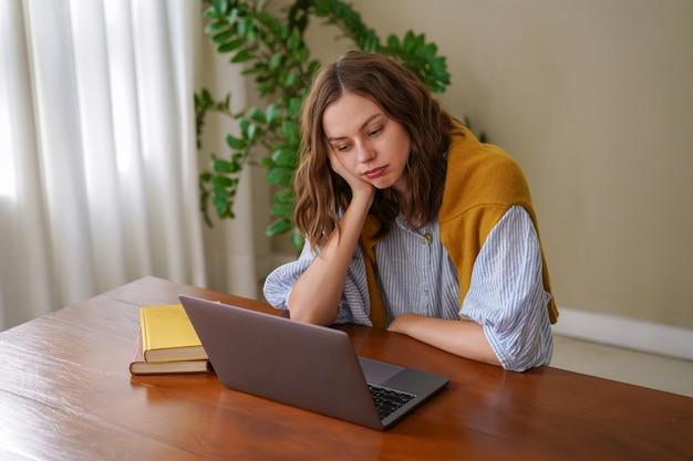 Молодая женщина, работающая в домашнем офисе фрилансера, чувствует себя уставшей после работы