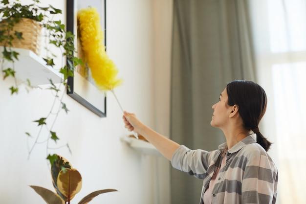 집에서 일하는 젊은 여자 그녀는 벽에 사진에서 먼지를 닦아