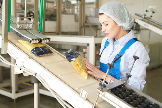 Молодая женщина работает на упаковочной линии