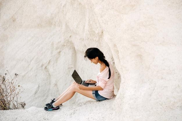 白い石の峡谷でラップトップで働く若い女性。フリーランスのコンセプト。